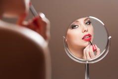 Blonde Schönheit, die auf Make-up sich setzt Stockfotografie