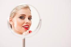 Blonde Schönheit, die auf Make-up sich setzt Lizenzfreie Stockfotografie