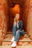 Blonde Schönheit, die auf Treppe in Trakai-Schloss sitzt Lizenzfreie Stockfotos