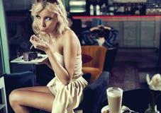 Blonde Schönheit, die einen Kuchen isst Stockfotografie