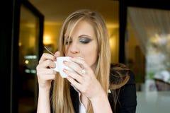 Blonde Schönheit, die etwas Getränk isst. Lizenzfreie Stockbilder