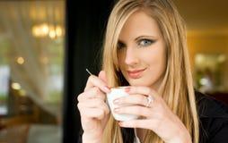 Blonde Schönheit, die etwas Getränk isst. Stockbild