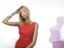 Blonde Schönheit, die rotes Kleid trägt Stockfoto
