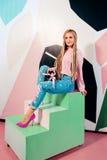 Blonde Schönheit mit den rosa afrikanischen Zöpfen, die schwarzen Präsentkarton halten Lizenzfreie Stockfotografie