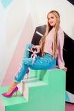 Blonde Schönheit mit den rosa afrikanischen Zöpfen, die schwarzen Präsentkarton halten Stockfotos