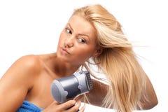 Blonde Schönheit mit Haartrockner Stockfotografie