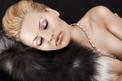 Blonde Schönheit Schlafens auf Pelz Stockfoto