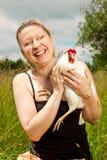 Blonde Schönheit umarmt ein weißes Huhn Stockbilder