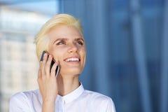 Blonde Schönheitsfrau, die Handy lächelt und verwendet Stockfotos