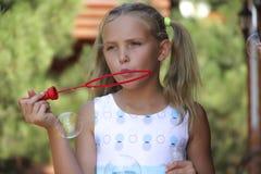 Blonde Schlagseifenblasen des kleinen Mädchens Stockfotografie