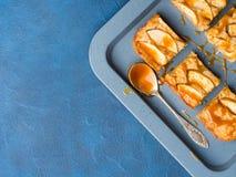 Blonde Schokoladenkuchen Apples mit Karamell auf Behälterblauhintergrund Stockfoto