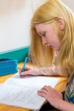 Blonde schoolgirl making homework Royalty Free Stock Photography