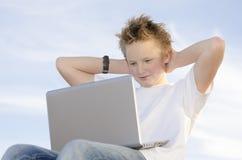 Blonde schooljongen het ontspannen handen achter zijn hoofd Stock Afbeelding