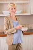 Blonde Schwangerschaft, die an der Kamera und am Essen lächelt Lizenzfreie Stockfotografie