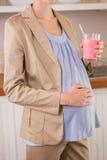 Blonde Schwangerschaft, die einen Smoothie trinkt Stockfotografie