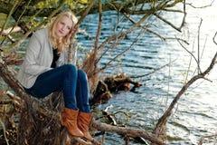 Blonde schwermütige Frau, die durch einen See sitzt Stockbild
