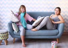 blonde Schwester des Jugendlichen in den Pyjamas auf dem Sofa Stockfotos