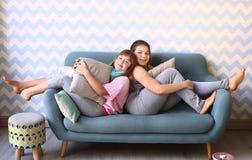 blonde Schwester des Jugendlichen in den Pyjamas auf dem Sofa Stockbild