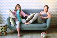 blonde Schwester des Jugendlichen in den Pyjamas auf dem Sofa Stockfoto