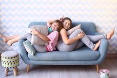 blonde Schwester des Jugendlichen in den Pyjamas auf dem Sofa Lizenzfreie Stockbilder