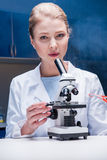 Blonde scientist working with microscope in laboratory, looking at camera Stock Photo