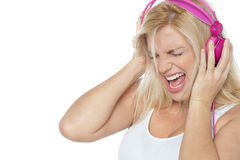 Blonde screaming while listening to rock music Royalty Free Stock Photo
