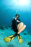 Blonde scuba diver swims in clear blue water