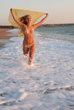 Blonde at the sea. Attractive young long-haired blond woman in bikini with yellow pareo is running along the coast Royalty Free Stock Photo