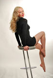 Blonde is seating on chair. Nice young blonde is seating on a chair stock photo