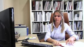 Blonde secretary receiving calls and writing notes stock video footage