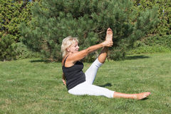 Blonde senior woman is exercising in the garden Royalty Free Stock Photography