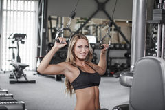 Blonde sexy bodybuilder pulldown practice in gym. Back, shoulder and triceps exercise Royalty Free Stock Images