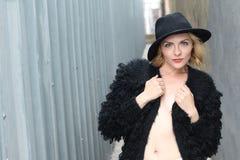 Blonde sexy Dame mit dem Zaubermake-up und langem Haar, die tragende schwarze Pelzjacke und einen Hut aufwerfen Lizenzfreie Stockbilder