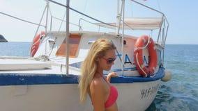 Blonde sexy dans les lunettes de soleil et le bikini rose posant à côté du bateau sur la plage banque de vidéos