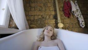 Blonde sexy de belle fille le matin posant dans la salle de bains action Jeune femme blonde se situant dans le bain dans image libre de droits