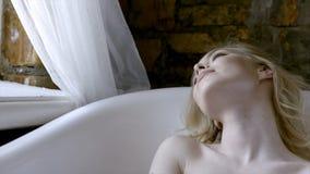 Blonde sexy de belle fille le matin posant dans la salle de bains action Jeune femme blonde se situant dans le bain dans photographie stock