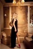 Blonde sexy Frau der High Society im langen schwarzen Kleid und im hohen Absatz Stockfoto