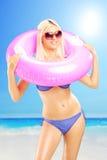 Blonde sexy Frau im Bikini, der einen rosa Schwimmring und ein enj hält Stockfotografie