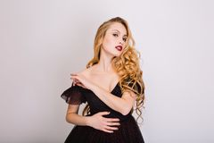 Blonde sexy girl, model with long beautiful curly hair posing at studio, sensually looking, flirting. Wearing black. Dress, has opened shoulders and bright royalty free stock photo