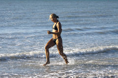 Blonde sexy Girl run in the Ocean Stock Images