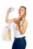 Blonde shopaholic vrouwenzakken en smartphone stock afbeeldingen