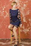Blonde with short hair in blue overalls with lace sleeves and sandals with high heels Royalty Free Stock Photos