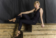 Blonde with short hair in blue overalls with lace sleeves and sandals with high heels Stock Photos