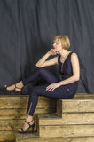 Blonde with short hair in blue overalls with lace sleeves and sandals with high heels Stock Image