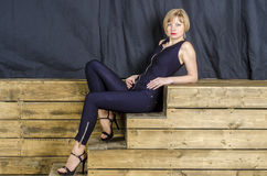 Blonde with short hair in blue overalls with lace sleeves and sandals with high heels Royalty Free Stock Image