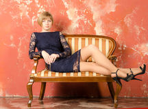 Blonde with short hair in blue overalls with lace sleeves and sandals with high heels Stock Photography