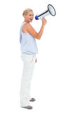 Blonde shouting through megaphone. On white background Royalty Free Stock Photography