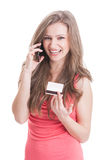 Blonde showing a credit card and talking on the phone Stock Photo