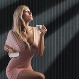 Blonde sinnliche Dame mit einem Cupkaffee Stockfotos