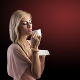 Blonde sinnliche Frau mit weißem Teecup Stockfotos